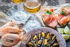 Seafood with two glasses of white wine on the wooden table Stock Photo