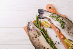 Seafood. Two raw rainbow trouts marinated with lime, rosemary. Seafood. Two raw rainbow trouts marinated with lime, peper, spices and rosemary on wooden board royalty free stock image