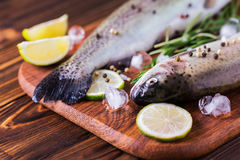 Seafood. Two raw rainbow trouts marinated with lime, rosemary. Seafood. Two raw rainbow trouts marinated with lime, peper, spices and rosemary on wooden board stock photos