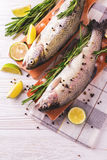 Seafood. Two raw rainbow trouts marinated with lime, rosemary. Seafood. Two raw rainbow trouts marinated with lime, peper, spices and rosemary on wooden board royalty free stock photo