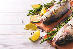 Seafood. Two raw rainbow trouts marinated with lime, rosemary. Seafood. Two raw rainbow trouts marinated with lime, peper, spices and rosemary on wooden board royalty free stock photos