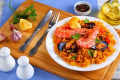 Seafood valencia paella on white plate. Portion of gourmet seafood valencia paella with king prawns, mussels on savory creamy saffron rice with spices and lemon Stock Photography