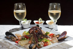 Seafood and white wine. Macro still life white dish with seafood and wine glasses with white wine on a white tablecloth in a studio on a black background Royalty Free Stock Photography