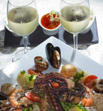 Seafood and white wine. Macro still life white dish with seafood and wine glasses with white wine on a white tablecloth in a studio on a black background Royalty Free Stock Photos
