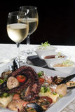 Seafood and white wine. Macro still life white dish with seafood and wine glasses with white wine on a white tablecloth in a studio on a black background Royalty Free Stock Photo