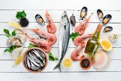 Seafood on a white wooden background. Fresh fish, shrimp, oysters and caviar. Top view. Free copy space stock photos