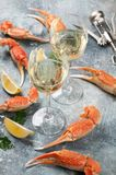 Seafood and wine. Lobster with lemon and white wine glasses. On stone table Royalty Free Stock Image