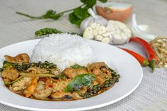 Seafoods cooked with thai spicy paste and thai harb. On white dish Royalty Free Stock Images
