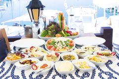 Seafoods, fish, salad and mezes on the table near the sea royalty free stock photos