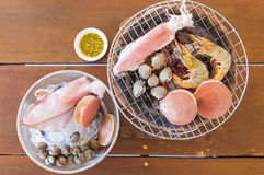 Seafoods grill on flaming grill. Seafoods grill on flaming grill on the wood table Royalty Free Stock Photography