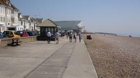 Seaford Sussex do leste com os visitantes que andam na luz do sol no passeio da frente marítima filme