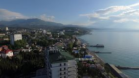 Seafront of Alushta in Crimea from drone in spring with piers cuts Black sea. Seafront of Alushta in Crimea from drone with piers cuts Black sea stock video footage