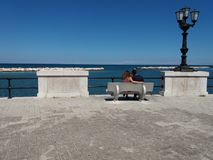 Seafront in the city of Bari. Southern Italy, with a pair of boyfriends sitting on the bench Royalty Free Stock Image