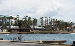 The seafront and harbour in Paphos Cyprus with promenade palm trees and buildings with bicycle parked on railings royalty free stock photos