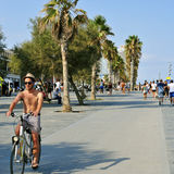 Seafront of La Barceloneta in Barcelona, Spain. BARCELONA, SPAIN - AUGUST 19: A young man rides a bicycle and some people walk in the seafront of La Barceloneta royalty free stock images