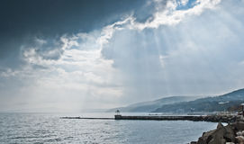 Seafront with mountains and rain clouds stock images