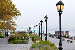 Seafront of New York city on day with heavy fog in autumn, Battery Park. Royalty Free Stock Photos