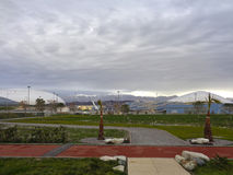 Seafront promenade and Sochi Olympic Park. Sochi Olympic Park, view of the seafront promenade, snow-capped mountains on the horizon, cloudy sky Royalty Free Stock Image