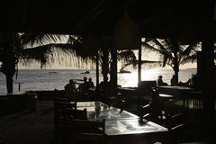 Tropical Seafront Restaurant, Bar Terrace, Friends Silhouettes at Sunset Royalty Free Stock Photography