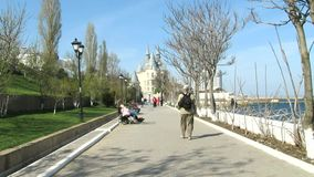 Seafront In The Spring. Sunny Day. People Walk And Relax. Calm sea. The beautiful castle is in the distance stock footage
