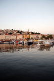 Seafront view with motor boats in Mali Losinj harbour,Croatia. Early sunset in Mali Losinj harbour with the motorboats and houses in background Stock Photo