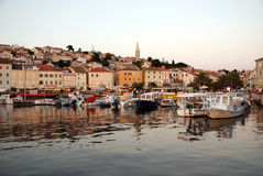 Seafront view with motor boats in Mali Losinj harbour,Croatia. Early sunset in Mali Losinj harbour with the motorboats and houses in background Stock Image