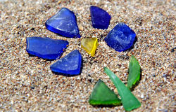 Seaglass flower. Pieces of sea glass arranged in a flower pattern on sand stock photos