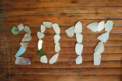 Seaglassdecor op houten achtergrond 2017 nieuwjaar overzees glasmozaïek Stock Afbeeldingen