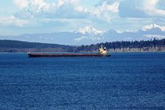 Seagoing Cargo Ship in Puget Sound. Seagoing vessel transports cargo through sapphire-blue water of Puget Sound with snow-capped mountains visible in background Royalty Free Stock Photography