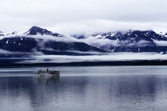 Seagoing Ship in a Cloudy Mountain Landscape. A solitary ship on a sea. Cloud-lined mountains rise up in the background Stock Photography