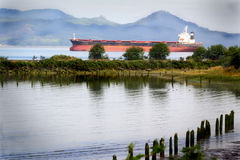 Seagoing ship on the river. A seagoing ship traveling up the Columbia River. Shallow depth of field Royalty Free Stock Images