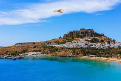 Seagull flies over a beautiful cove beach Lindos acropolis ships dock Royalty Free Stock Photo