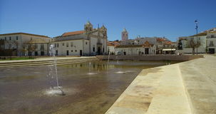Seagull flies on the square, and the church of Santa Maria in Lagos Portugal Algarve. Seagull flies over the fountain on the square, and the church of Santa stock footage