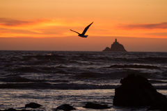 Free Seagull Flying In Front Of Distant Lighthouse At Sunset Royalty Free Stock Image - 89617886