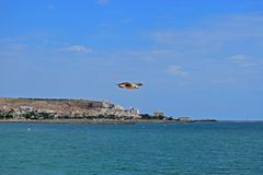 A Seagull Gliding Near Land In A Blue Cloudy Sky stock photo