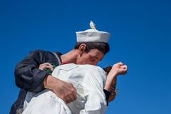 Seagull sitting on statue depicting Alfred Eisenstaedt`s picture of a U.S. Navy sailor passionately grabbing a passing woman royalty free stock photos
