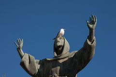 Seagull on st. Francis statue in Piazza San Giovanni, Rome, Italy. Seagull stay on the head of st. Francis statue in Piazza San Giovanni, Rome, Italy Royalty Free Stock Image