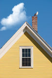 Seagull on yellow gable. Seagull resting on chimney on house with yellow gable against blue sky with clouds Royalty Free Stock Image