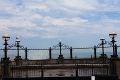 Seagullen sitter på kusten Havvågor som slår kusten Blå himmel med moln i bakgrunden Ljusa lampor på kusten C arkivbild