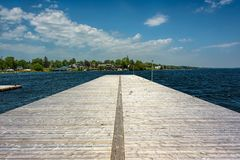 Seagulls on a wooden pier under blue skies. With fluffy white clouds Royalty Free Stock Photo