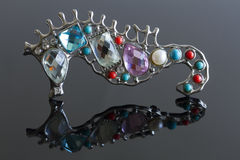 Seahorse brooch. Fashion jewelry : a brooch shaped like a seahorse with several different gems and stones in it. Reflection on silvery ground royalty free stock image