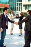 Seal The Deal. Two Businessmen shake hands on a deal and two women celebrate the deal in the background Stock Photos