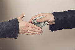 Seal the deal. Detail of two business people sealing the deal with bribe money. Selective focus Stock Image