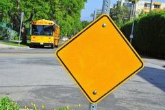 Señal y autobús escolar en blanco de tráfico Fotografía de archivo libre de regalías