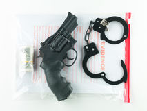 Sealed bag of evidence. Aerial view of a bag marked evidence containing a roll of money, a revolver and a pair of handcuffs with their keys, on a white stock photography