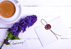 Sealed letter on a white wooden surface, near a lilac bud and a Royalty Free Stock Photo