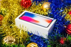 A box with a smartphone in a Christmas tree tinsel. A sealed smartphone lies in Christmas toys Stock Photos
