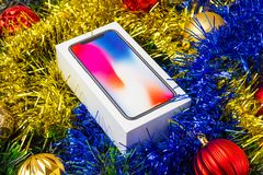 A box with a smartphone in a Christmas tree tinsel. A sealed smartphone lies in Christmas toys Stock Photography