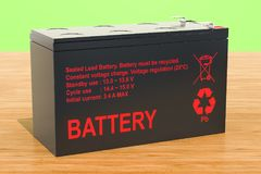 Sealed UPS battery on the wooden background, 3D rendering. Sealed UPS battery on the wooden background, 3D Stock Photos
