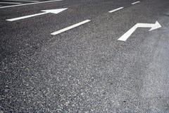 Señales de tráfico pintadas en camino Imagenes de archivo